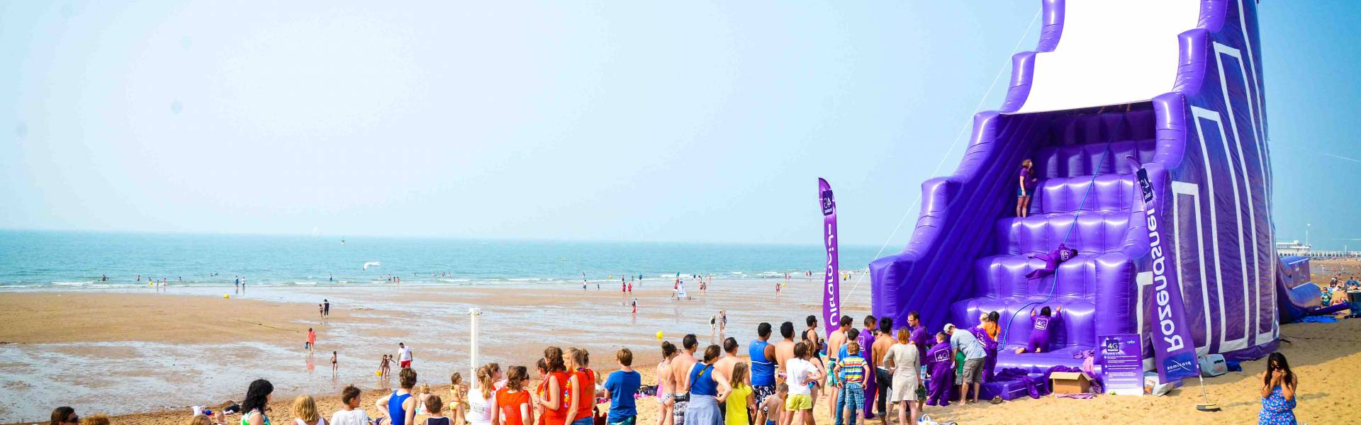 Large inflatable promotional material | X-Treme Creations Purple inflatable slide on the beach with the slogan: 4G to 10 times faster and the Proximus logo. Proximus Demonstr8 X-Treme Creations