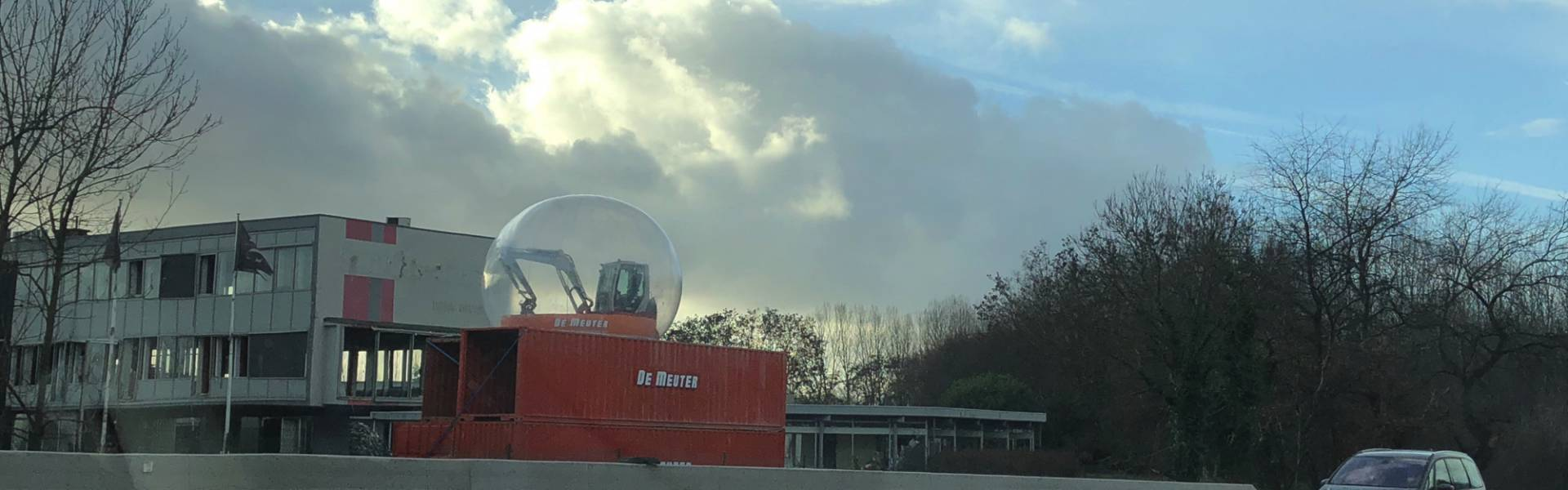 Large inflatable promotional material | X-Treme Creations Transparent bubble of 6m located on a 5m high platform of 40 and 20 foot red containers with an excavator in it De Meuter Wave X-Treme Creations