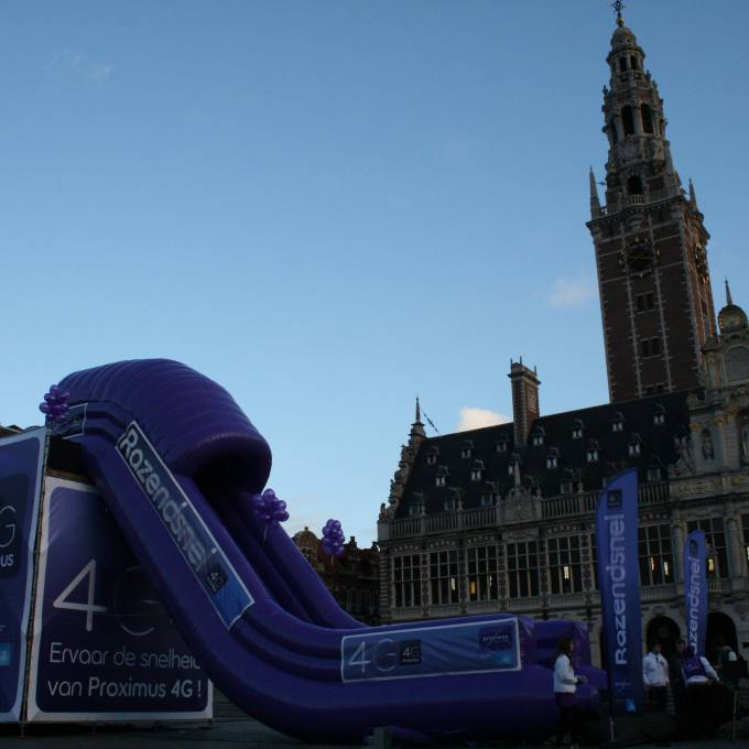 Large inflatable promotional material | X-Treme Creations Purple inflatable slide with the slogan: 4G to 10 times faster and the Proximus logo placed in front of a church Events  & Corporate branding  & Brand activation  &  Proximus Demonstr8 X-Treme Creations
