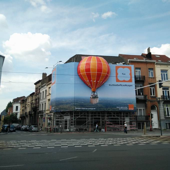 Groot opblaasbaar promotiemateriaal | X-Treme Creations Rood-oranje opblaasbare  luchtballon die in de muur zit door combinatie van 2D en 3D Bedrijfsidentiteit  & Merkactivatie  &  Orange Pop-Media X-Treme Creations