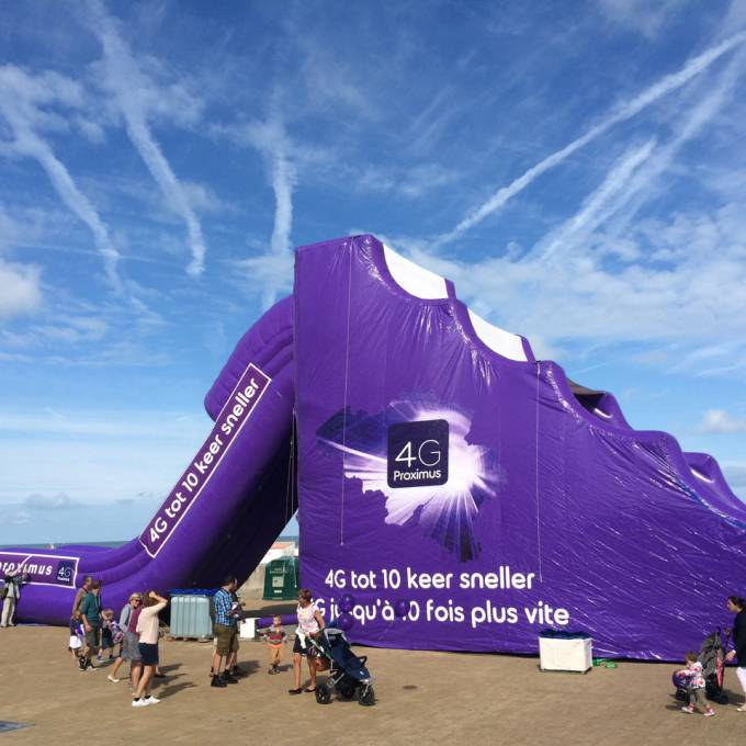 Large inflatable promotional material | X-Treme Creations Purple inflatable slide on the beach with the slogan: 4G to 10 times faster and the Proximus logo. Events  & Corporate branding  & Brand activation  &  Proximus Demonstr8 X-Treme Creations